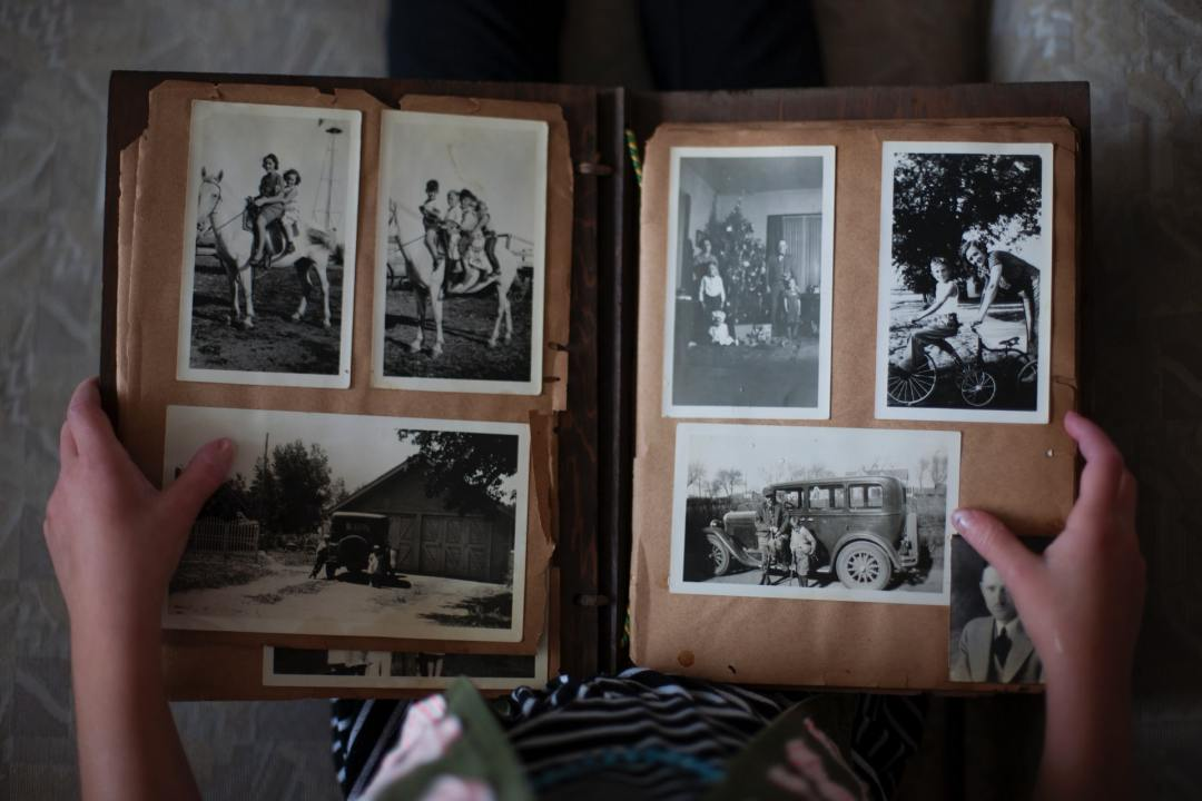 Image of person looking at a photo album of memories.