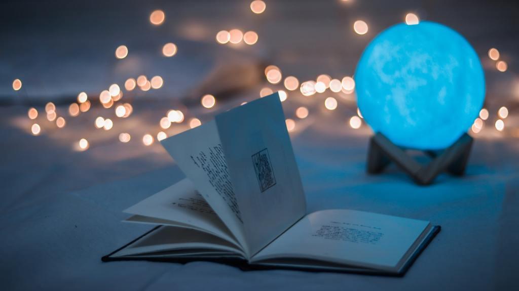 open book beside crystal ball working editing magic