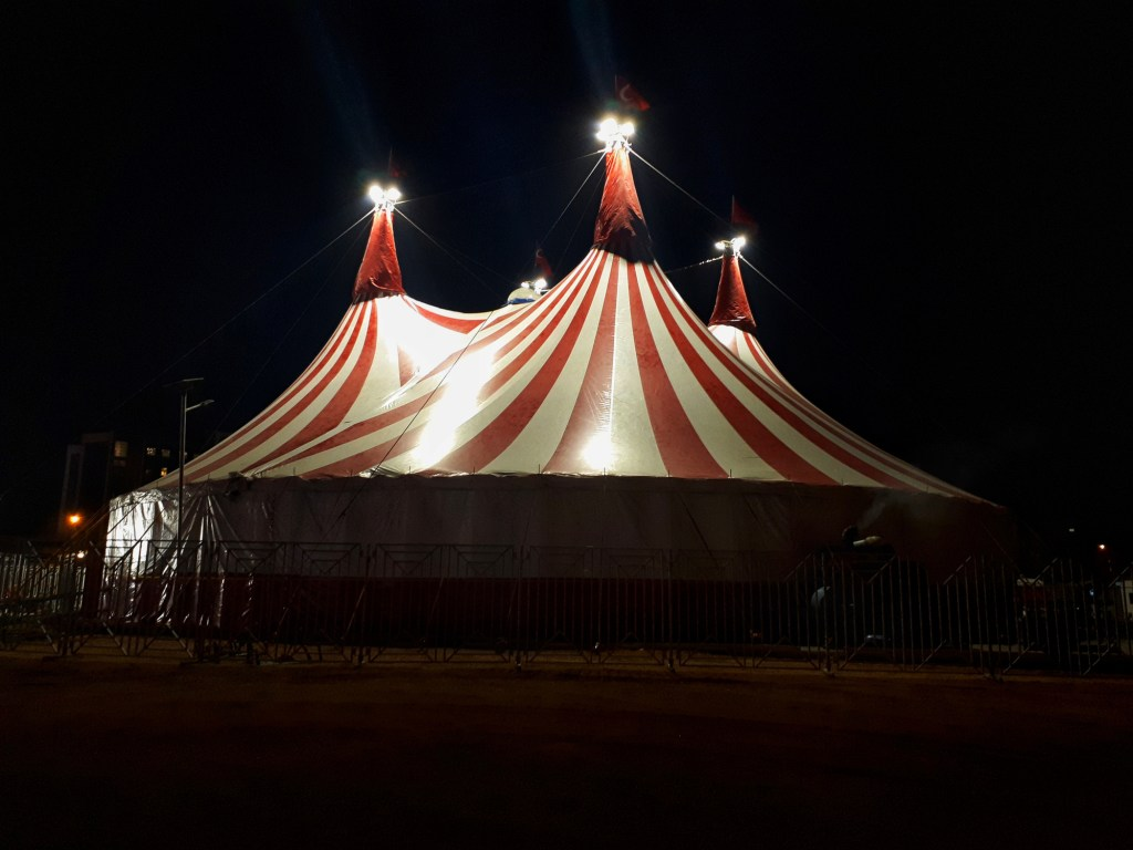 red and white striped circus tent at night