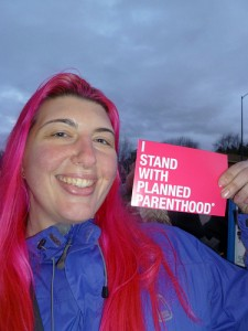 A pink-haired activist holds up a small card, I Stand With Planned Parenthood.