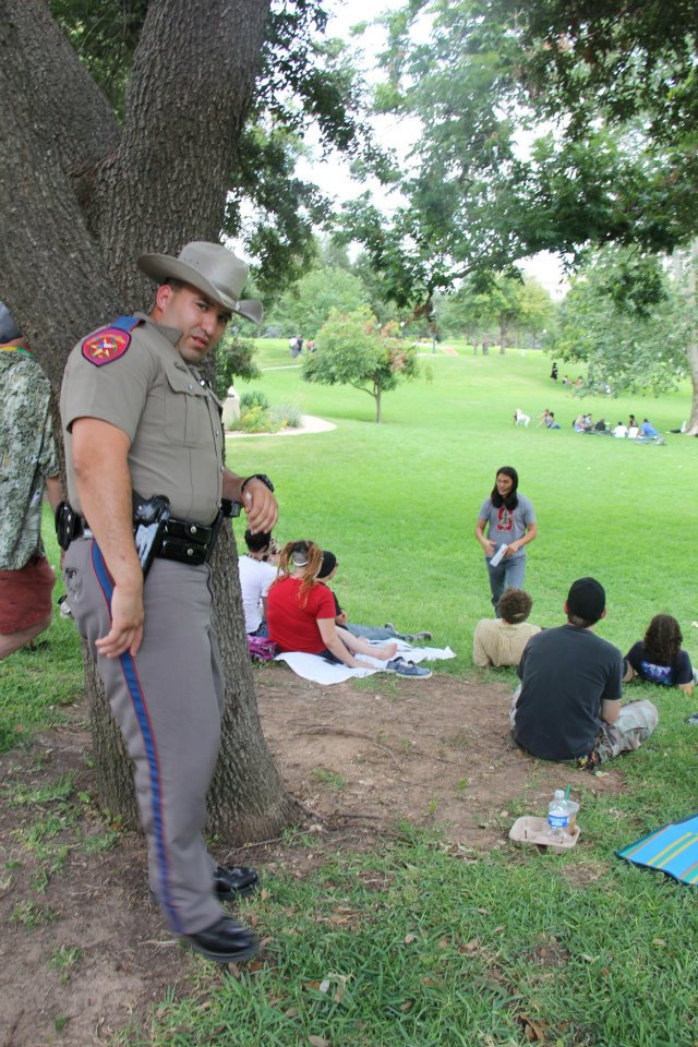 A state trooper leans against a tree as he listens to a class.