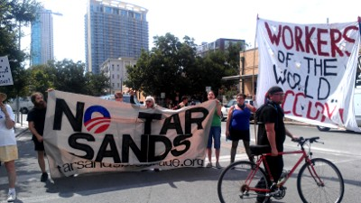 Two protest banners: No Tar Sands & Workers of the World Occupy!