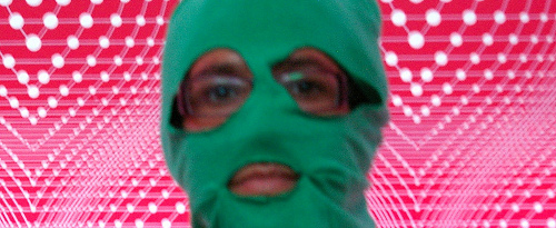 A woman in a colorful green balaclava against a psychedelic pink background