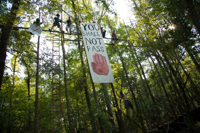 """A banner hanging from a tree blockade in the Texas forest reads """"You Shall Not Pass"""" with a graphic of a hand showing the gesture for 'Halt.' (Above All Else publicity still)"""