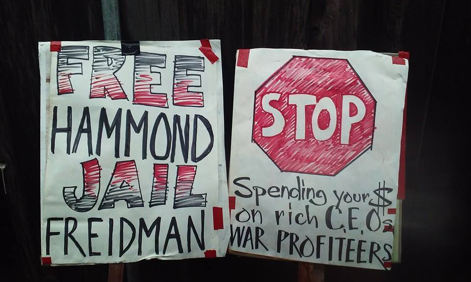 "Two picket signs prepared for George Friedmain's book signing in San Francisco. One reads, ""Free Hammond, Jail Friedman."" Another: ""STOP Spending Your $ On Rich CEOs and War Profiteers."" (Ronin)"