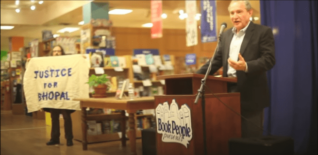 """In this Feb 2. 2015 photograph, George Friedman, CEO of Strategic Forecasting, speaks at a podium while Kit O'Connell stands nearby with a banner reading """"Justice for Bhopal,"""" at BookPeople in Austin, Texas. (YouTube screenshot)"""