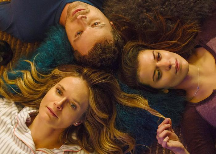 From left to right, Emma (Rachel Blanchard), Jack (Greg Poehler) and Izzy (Priscilla Faia) lay in a circle with their heads together, as Izzy plays with a lock of Emma's hair. (You Me Her publicity still)