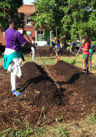 Young people prepare garden beds at the Hamilton Heights community garden. (American Friends Service Committee)