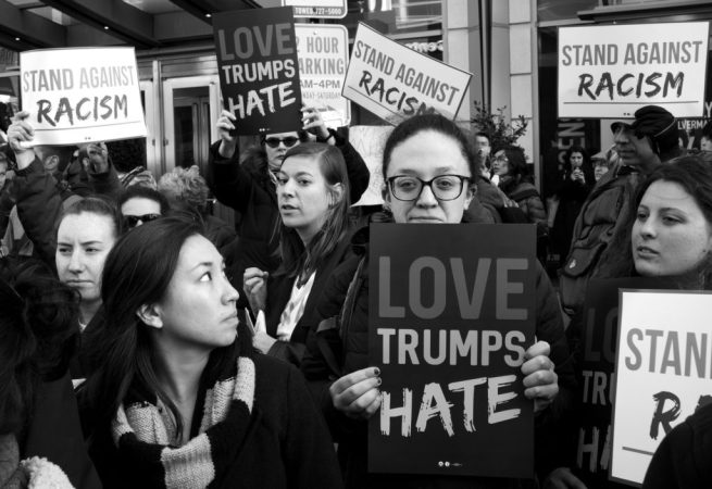 """Protesters hold signs reading """"Love Trumps Hate"""" and """"Stand Against Racism"""" during Donald Trump's speech to AIPAC. March 21, 2016. (Flickr / Stephen Melkisethian)"""