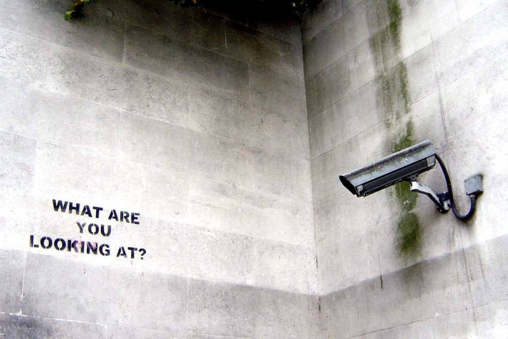 "A stencil by Banksy on a wall opposite a surveillance camera reads, ""What are you looking at?"" (Flickr / nolifebeforecoffee)"