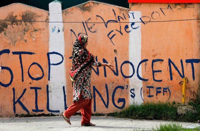 A Kashmiri woman walks past graffiti demanding freedom for Kashmir. (Flickr / Kashmir Global)