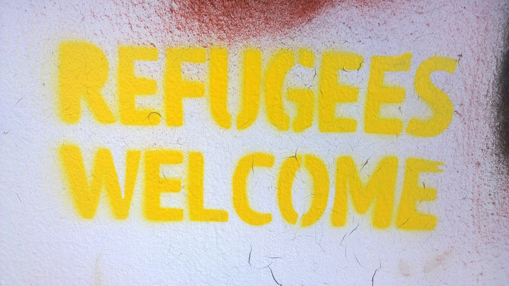 "A graffiti stencil on a wall reads ""REFUGEES WELCOME"" in yellow. paint. Journalism should scare the powerful and help the powerless. The Project Veritas Cycle does the opposite."