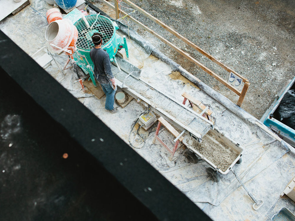 A man works on a conveyor belt spreading hempcrete into a home.