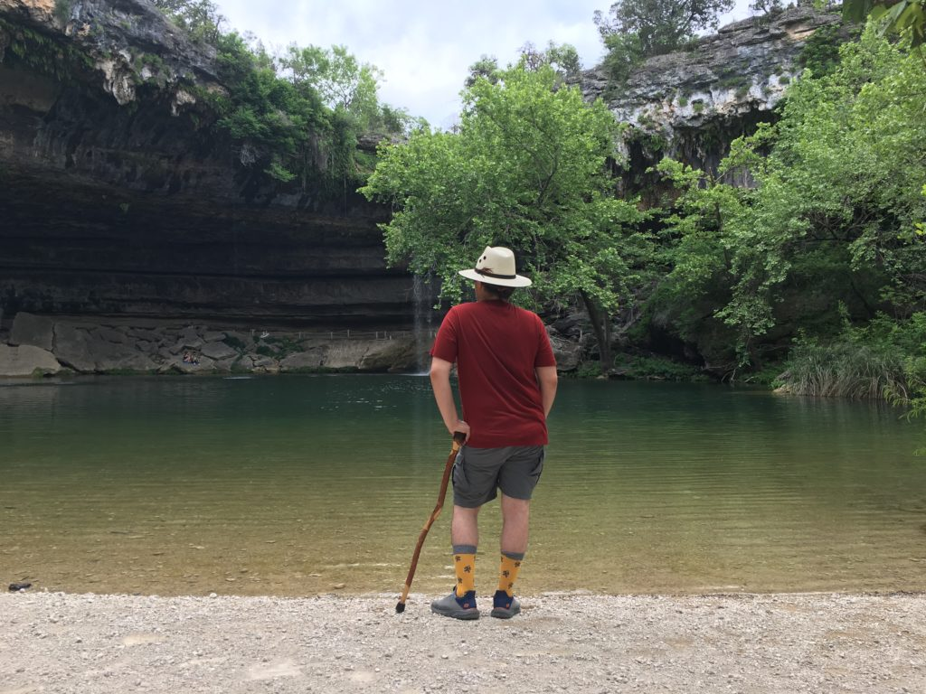 Kit stands on the edge of a natural pool surrounded by greenery and an overhanging cave. Seen from behind, he leans on a hand-carved cane and is wearing gray shorts, a red t-shirt, a white panama hat, and yellow bigfoot socks.