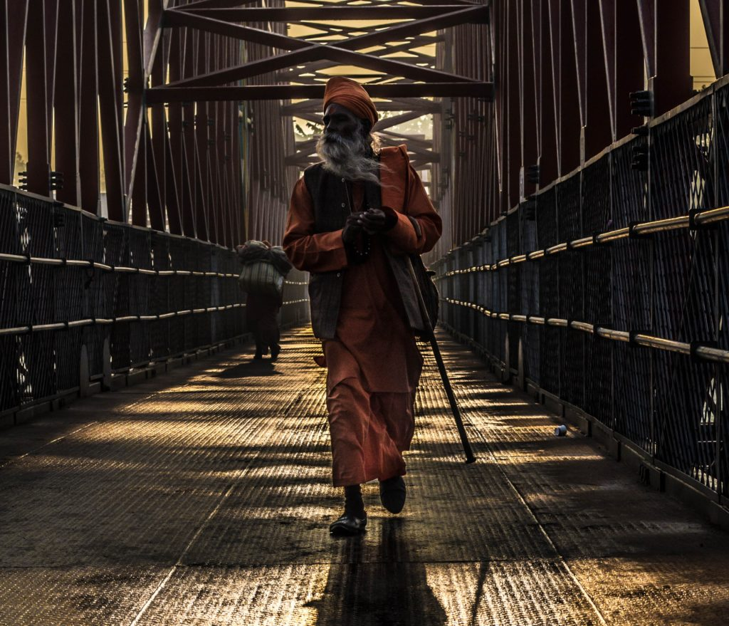 A sikh walks across a bridge, holding a cane in an arm but not using it to walk.