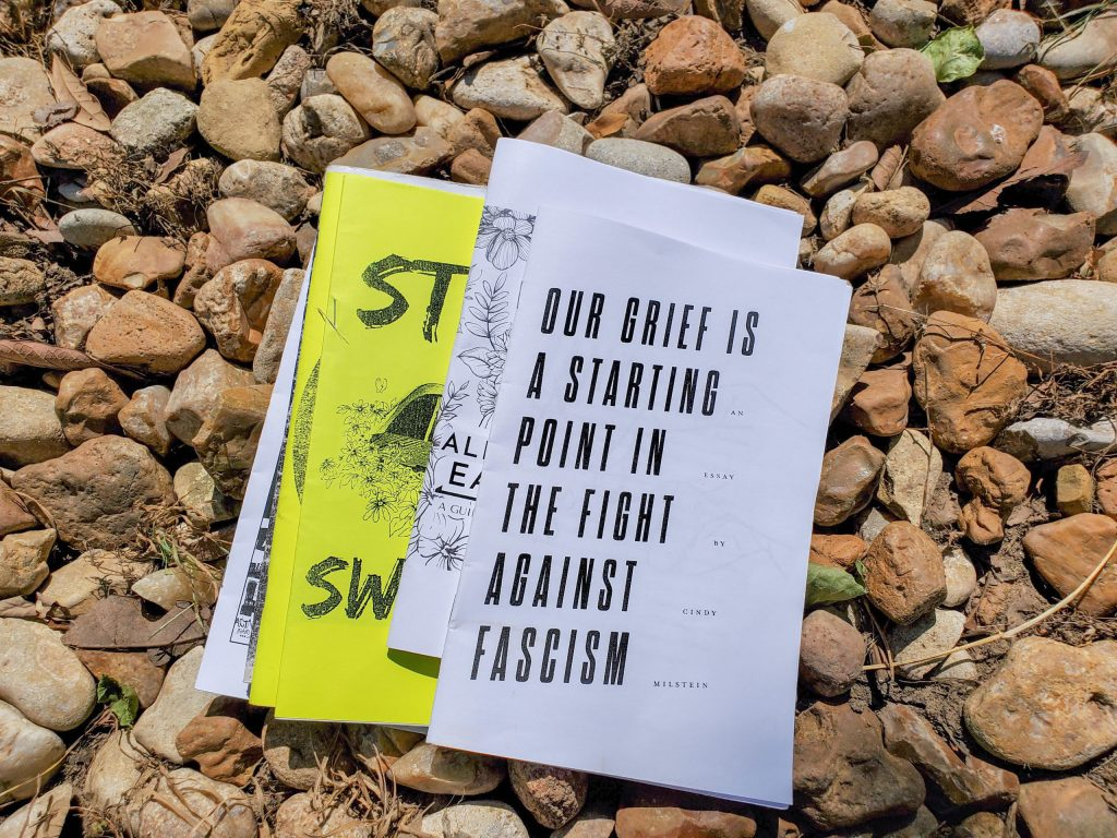 Photo: A collection of zines sitting on a bed of gravel.