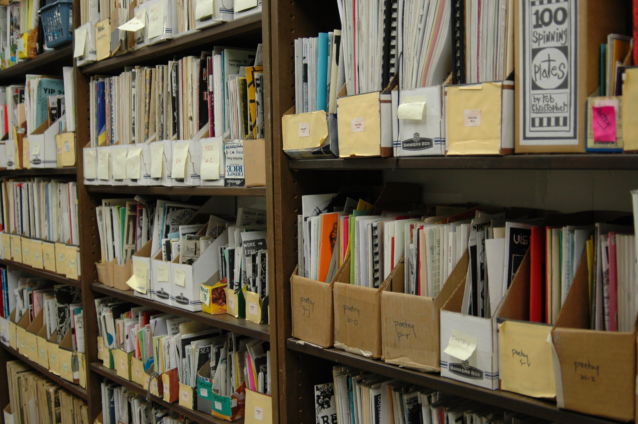 A large zine library in Denver, with rows of paper zines in magazine holders, organized by subject and alphabet.