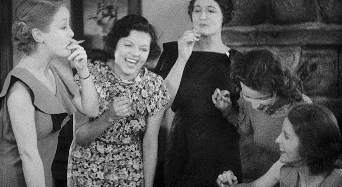Film still: A fivesome of ladies in 50s cocktail dresses laugh uproariously as they smoke cannabis cigarettes.