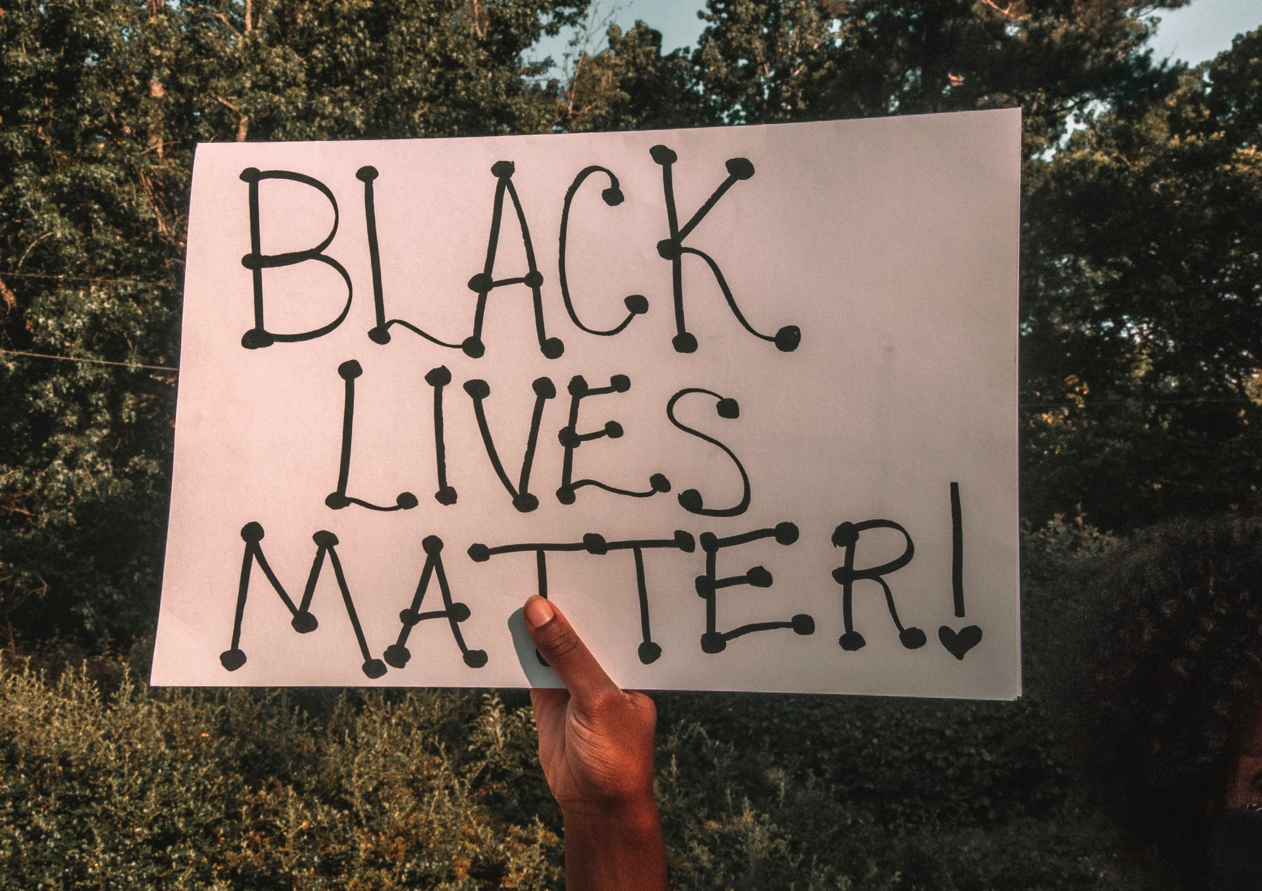 Photo: A black person's hand holding up a handmade Black Lives Matter sign, against a natural looking background.