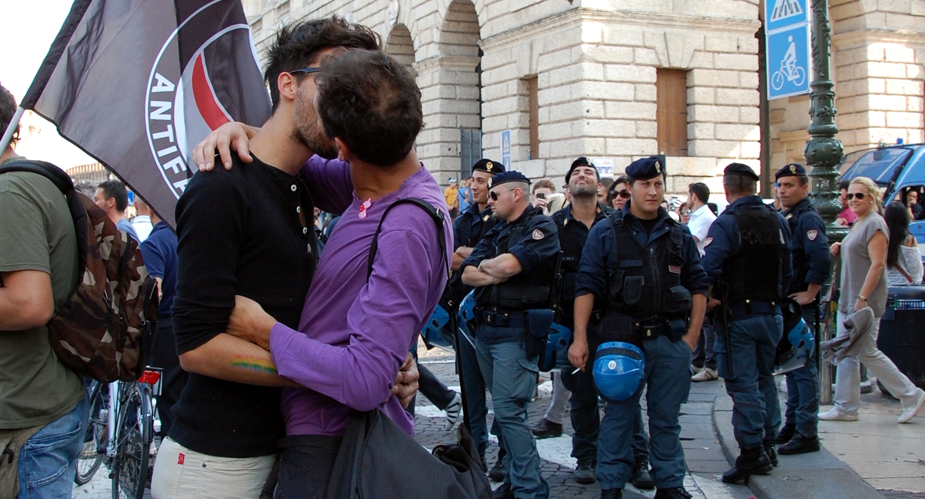 A queer couple embrace in front of an antifa flag at a protest, as police look on. Vienna, Italy 2013.