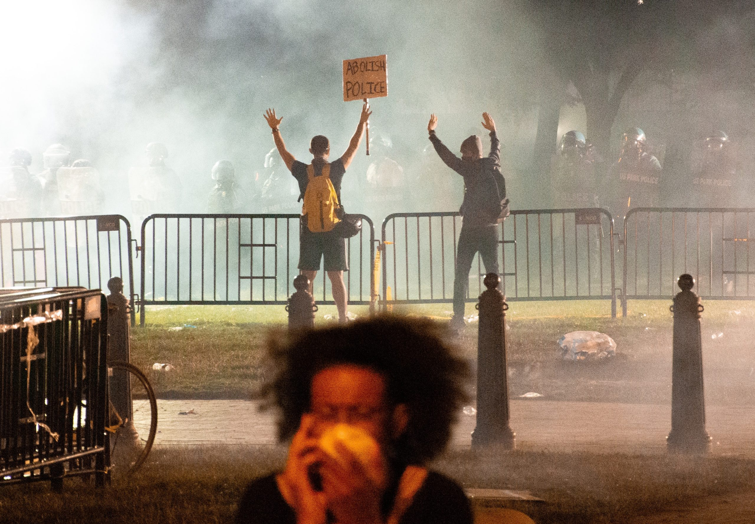 A chaotic protest scene cloudy with tear gas. In the foreground a woman wears a gas mask and looks distresed. In the background, two protesters confront a row of riot cops with an abolish police sign.