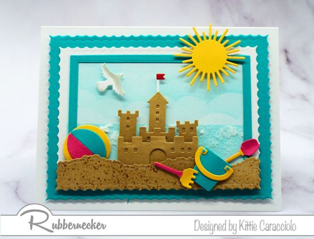 Make a sandcastle beach card with a sparkly ocean background using dies made by Rubbernecker Stamps.