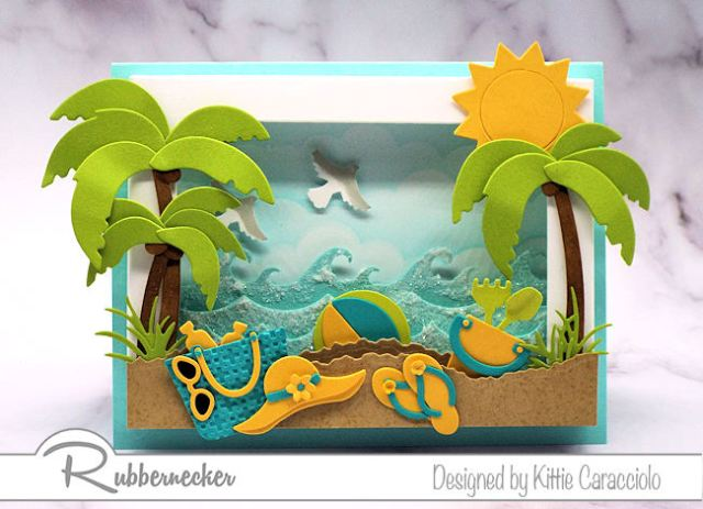 This shadow box frame beach scene is so inviting with the colorful beach accessoires and sparkling ocean waves.