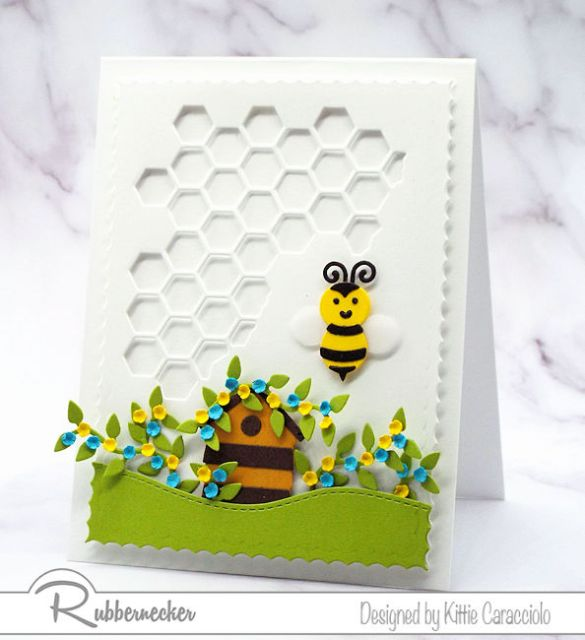 A paper pieced handmade greeting card featuring a bumblee and a die cut honeycomb background.