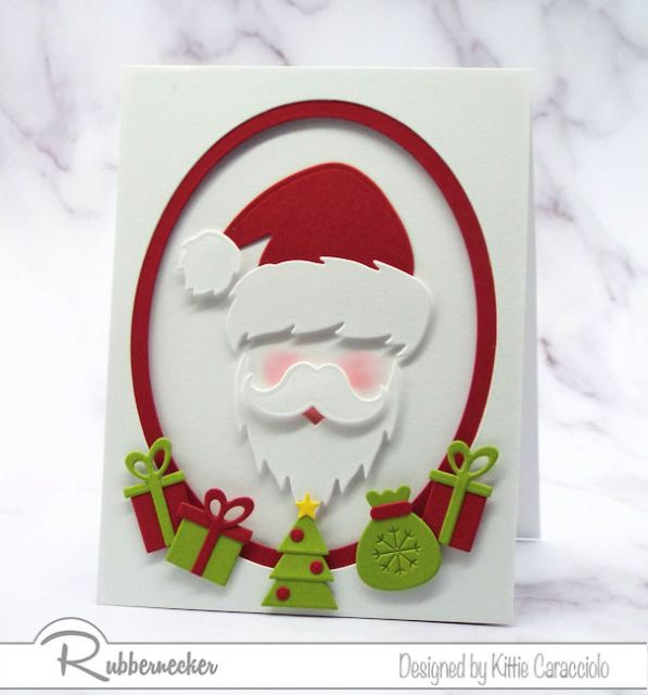 One of my santa Christmas cards showing a die cut santa face in an oval window surrounded by die cut gifts on a handmade card