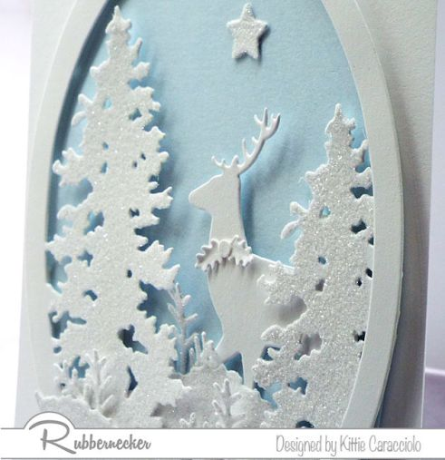A details image of my white on white Christmas card idea showing the layering of the evergreen trees, greenery and a deer all in white using die cuts from Rubbernecker