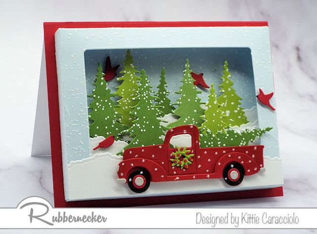 a shadow box card die cut and assembled to show off the dimension in a card featuring a classic red pickup and wintry forest all made using die cuts from Rubbernecker