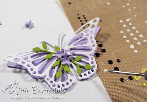 Die cut butterfly embellishments are enhanced with small stems and flowers.