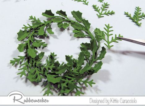Learn how to make a wreath with die cuts as depicted here as layers of die cut greenery is attached to a base of die cut paper