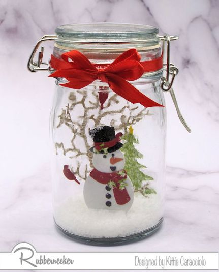 Learn how to make a snow globe in a mason jar like this one featuring die cut images and fake snow