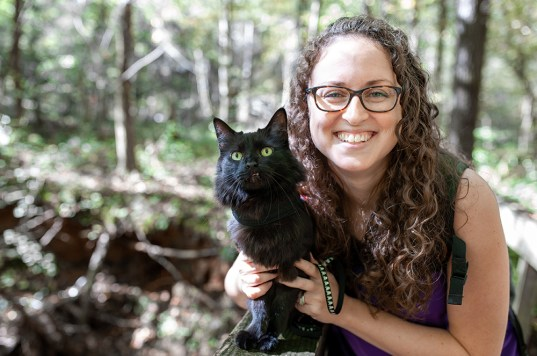 Woman and black cat in the woods
