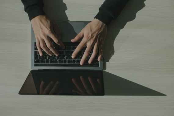 hands typing on a laptop keyboard