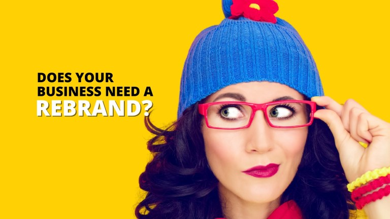 woman with pink glasses and a blue tuque looking to the left and thinking if her business is in need of a rebrand
