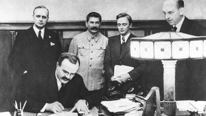Utrikesminister Molotov undertecknar den s.k. Molotov-Ribbentroppakten i Moskva den 23 augusti 1939. Bakom honom t v står utrikesminister Ribbentrop och Stalin.