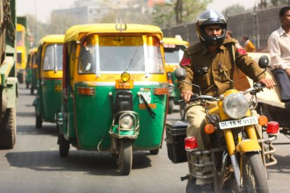 Ein Motorradpolizist uberholt unsere Kolonne von Autorikschas in Delhi