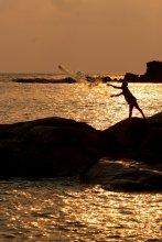 Ein Fischer wirft sein Netz aus am Patnem Beach