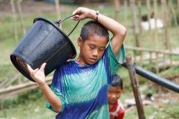 Kinder beim Wasserholen in Na Dao, Laos