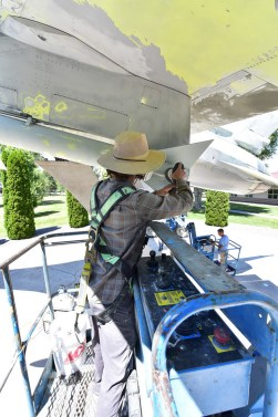 A Ponsford restorer works on grinding paint on the F16 Fighting Falcon display jet in preperation for a fresh coat of paint at Kingsely Field Air National Guard Base on July 2, 2019. These jets are on loan from the Museum of the US Air Force, and are getting their first full refresh in 15 years.