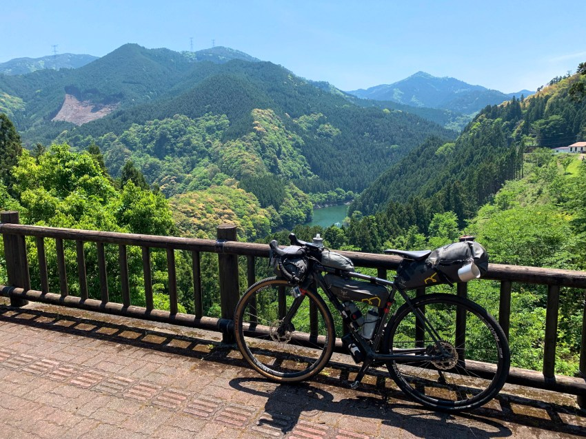 Bicycle on a platform overlooking a river valley with mountains covered in forest vegetation