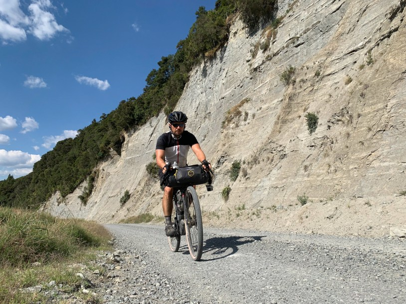 Cyclist on a gravel road, next to a steep cliff