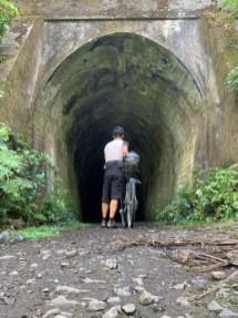 Cyclist pushing bike through former railway tunnel along cycling trail
