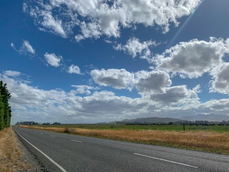 Flat stretch of road with farmland stretching into the distance