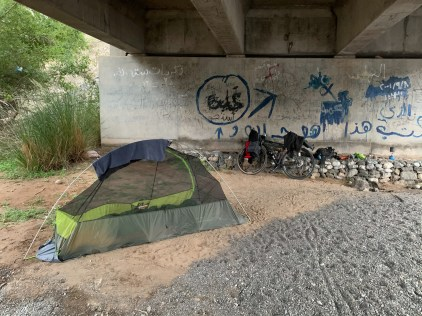 Camping in an almost dry riverbed, underneath a bridge