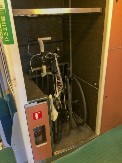 The bike securely stored in a small luggage space on the train