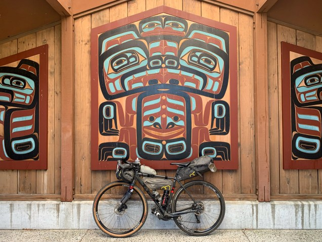 bike leaning against indigenous wood carving wall art