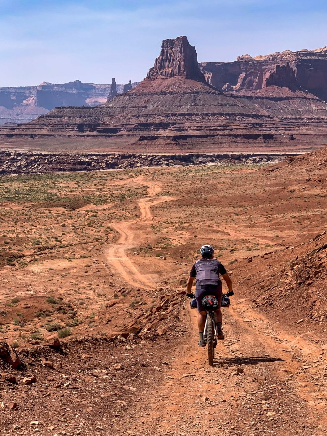 Ethan heading downhill on the dirt road with the butte rock formation called Airport Tower in the distance